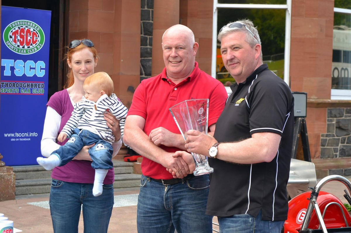 Gerard O'Connell {R} receives the winners trophy from Simon McKinley's father Peter, his widow Diedre and baby son Rory